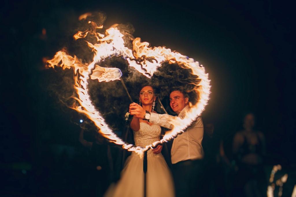 Egy házaspár meggyújt egy szivet, mely lángol előttük.