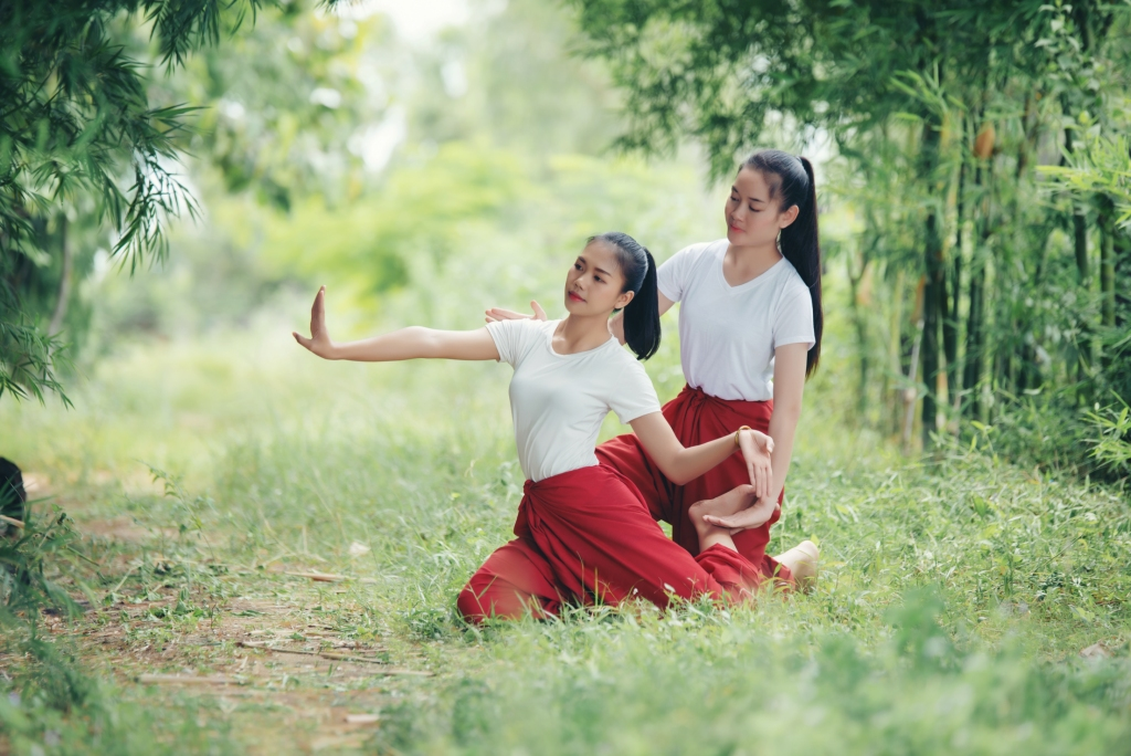 Két thai lány ősi rituális mozdulatokat végez az erdőben.