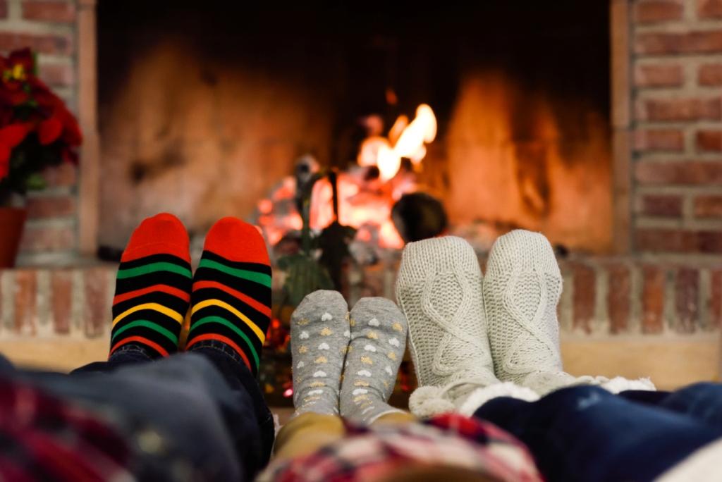 Egy apa, egy anyag és egy gyerek a zoknis lábát melegíti a kandallónál