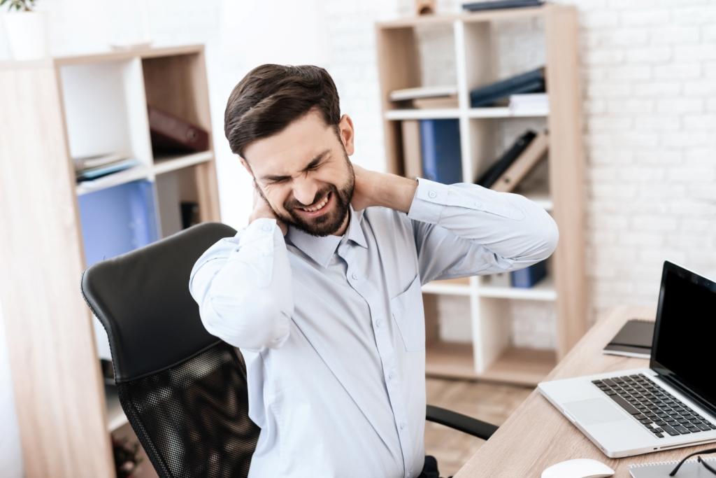 Szakállas férfi ül a laptop előtt és próbálja kilazítani a fájós nyakát.