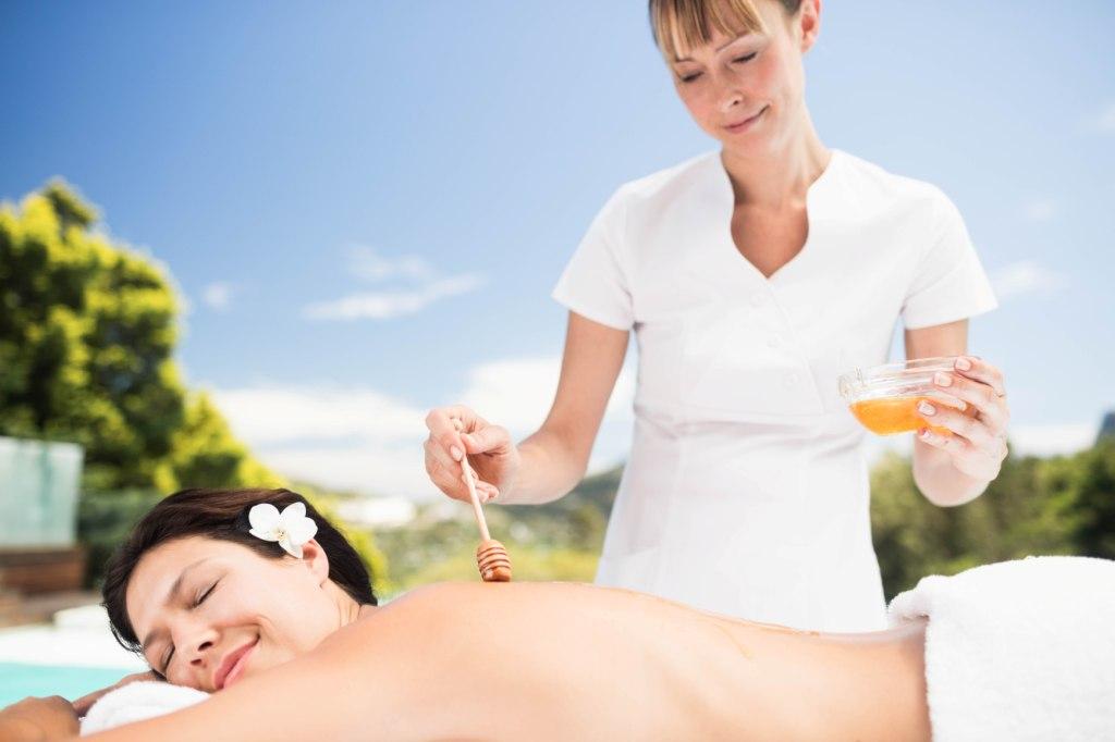 Egy női terapeuta mézet csorgat egy üveg tálkából a vendég hátára. Távolabbi kép.