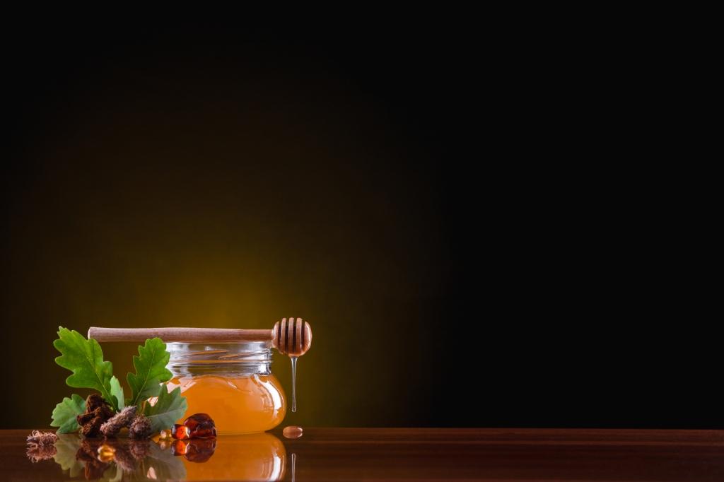 Üveg, csavaros tetejű mézes csupor, tölgyfa levelek, és egy mézadagoló pálcika. sötét háttér előtt.