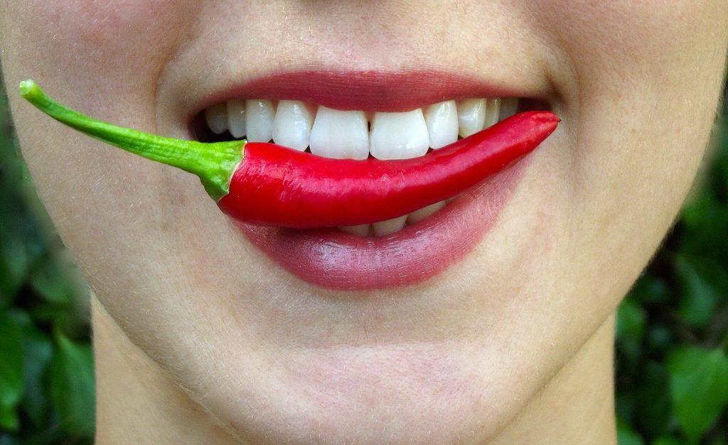 Piros női száj. A fogai között egy pirospaprikaát tart.