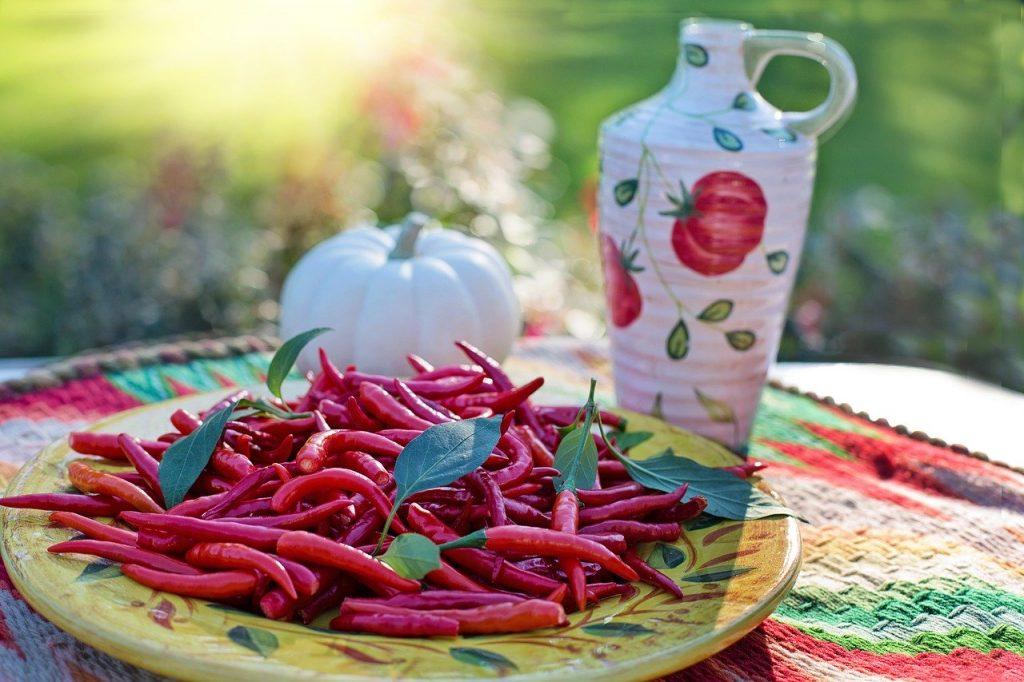 Mexikói hangulatú tál, terítő és kancsó. Egy fehér tököcske, és  jalapeno paprika a tálon.