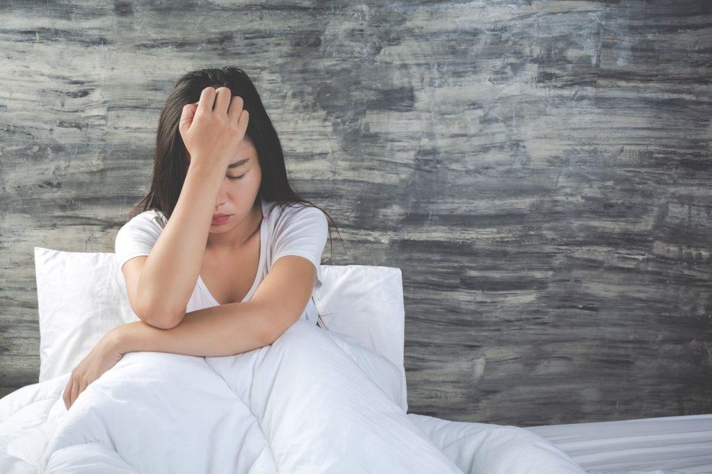 Szürke fal előtt fehér ágyneműben, fehér pólóban feketehaú nő ül. Fogja a fejét, jelzi, hogy fáj neki.