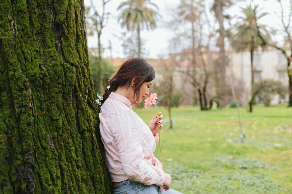 Mohás fa törzséhet támaszkodó fonott hajú lány, virágot szagolva.