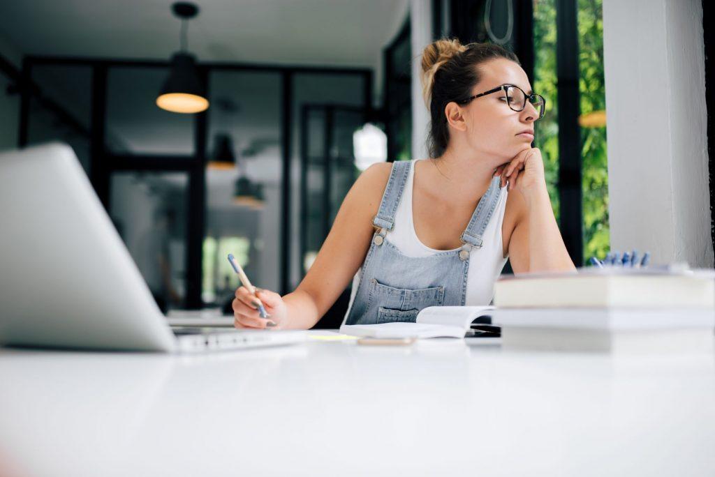 Fiatal, szemüveges lány ül a laptop előtt és kinéz az ablakon.