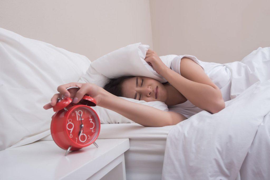 Fehér ágyneműben fejére párnát húzó nő lenyomja a piros ébresztőóra gomját.