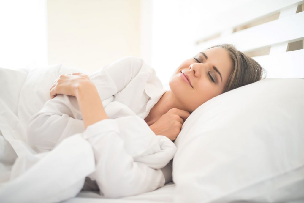 Mosolygó nő alszik fehér párnák között.