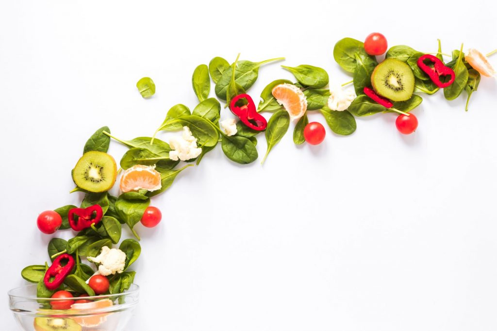 Üveg tálka, amelyből zöldségek, gyümölcsök futnak a levegőben.
