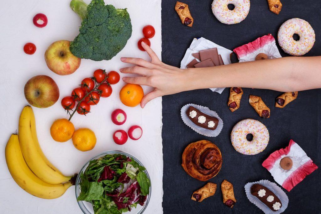 egy fekete fehér háttéren az egyik oldalon gyömülcsök, egészséges ételek, a másik oldalon fekete alapon sütemények, cukrok, csokoládé. Női kéz a narancs után nyúl.